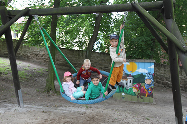 Vier Kinder in einer Nestschaukel